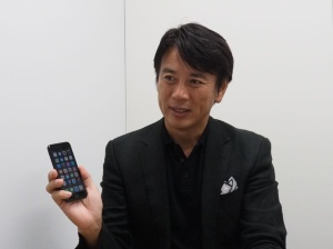 前刀禎明氏。手には現在愛用中のiPhone 7