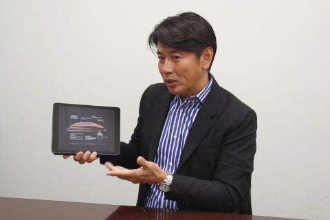 iPadでアップルのプレゼンを表示しながら語る前刀禎明氏
