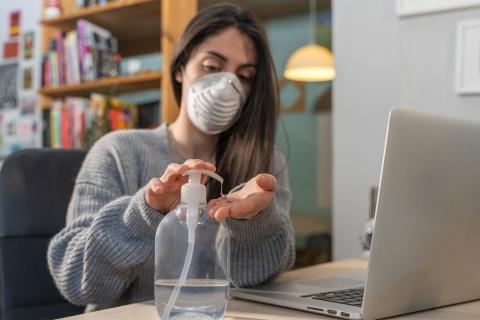 マスク着用で指先を消毒しながら在宅勤務(写真/Shutterstock)