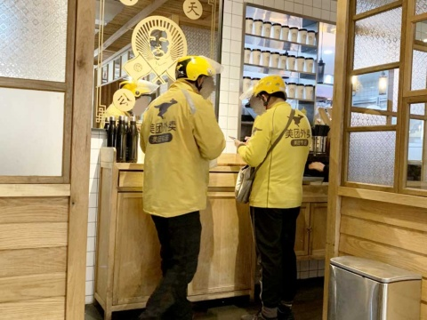 店内で配送商品を待っている美団外売の配送員たち