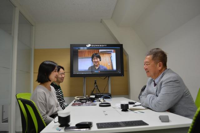 日本橋室町のダンクソフトのオフィス。星野CEO(写真右)とスタッフたち。中央画面は徳島市内のサテライトオフィスの様子