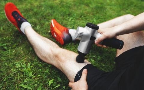 マッサージガンで足をマッサージするシーン(写真/Shutterstock)