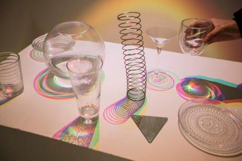 テーブルに置いてあるものに照射すると、影が多くの色に分かれ、今まで見たことがない光景が広がる