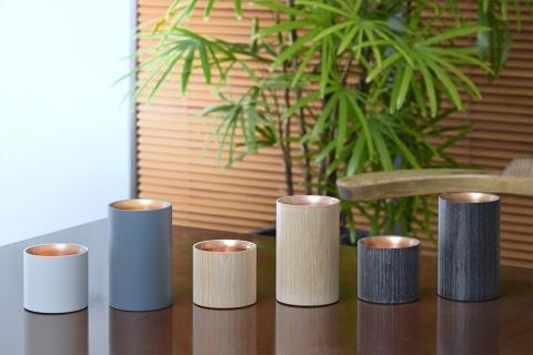 「POWER SPOT(パワースポット)」のカップ。長い「MUG」は好みの温度で飲み物を保温できるマグカップ。短い「CHOKO」はぬるかんの40℃から熱かんの60℃まで設定できる日本酒向けの器。材質は銅や木材、ベークライト。想定価格はMUGが2万7000円、CHOCOが2万4300円を予定