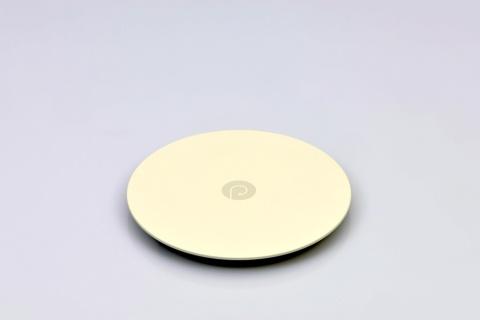 開発した円形の送電モジュール「HOME」。この上にカップや卓上照明を置いて使う。直径は約15cmで材質はABS樹脂やウレタン。価格は1万8600円ぐらいを予定