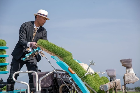 スーツ姿で作業する齋藤氏は、農業のイメージを変えることで若い人たちを取り込もうとしている