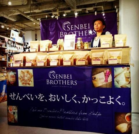 「センベイブラザース」を取り扱っている東京・秋葉原の「日本百貨店しょくひんかん」の店頭風景。紫色はせんべいの醤油(しょうゆ)を象徴するブランドカラーで、店頭では紫色のハットをかぶって目立つようにした