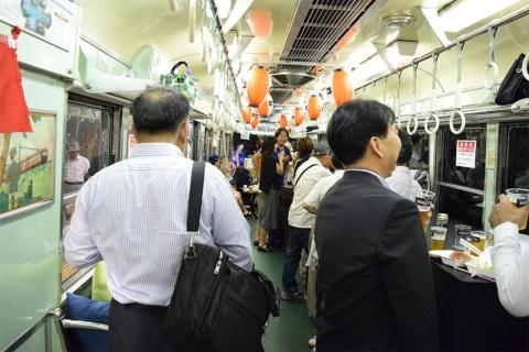 中之島駅ホーム酒場の様子。電車内で飲む来場者。右の窓側には電車が走っており、それを見ながら一杯やれるのだ