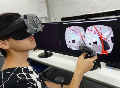 シナスタジアが開発している「RideVision」(ライドビジョン)を使うと、自動運転車向けVRコンテンツを制作できる。VRヘッドセットに付けた数個のセンサーの動きをモニター上のカメラで撮影して目で見ている方向を把握している