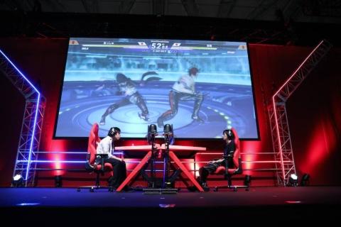 対戦はステージ中央で行われる。後方の巨大スクリーンにはゲーム画面が表示され、試合の展開を把握しやすい