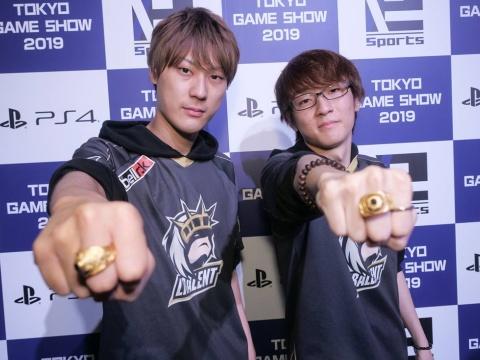 優勝賞品のチャンピオンリングを指にはめ、ポーズを決めるLibalent Vertexの2人。左がsitimentyo選手、右がxAxSy-選手