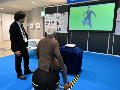 """圧力センサーシートとバランスボールを組み合わせた展示物。バランスボールに腰掛けた人の姿勢をモニター上の""""デジタルヒューマン""""で可視化する"""
