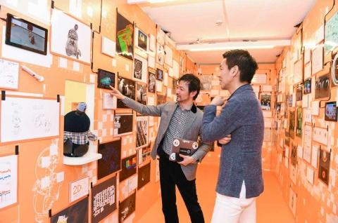 GROOVE X(東京・中央)の林要社長(左)の案内で「LOVOT」開発時の資料などを見る一休の榊淳社長