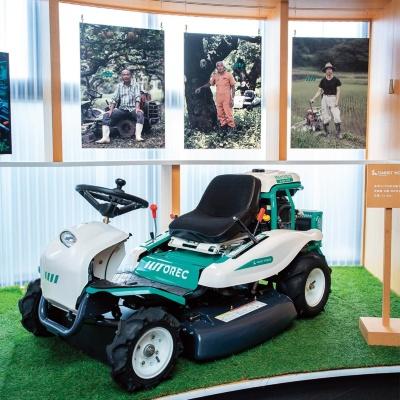 オーレック本社のエントランスには広いスペースが設けられ、来客者を迎え入れるように製品が展示されている。車体の色は、リブランディングの際にコンセプトモデルをつくり、ロゴと同じ緑色にそろえた。中央は2019年度グッドデザイン賞に選ばれた水田除草機「WEED MAN」(写真/林田大輔)
