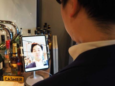 ロイヤルホールディングスによる顔認証決済の実証実験。タブレットのカメラで顔を向けることで、利用者を認証し、カードやスマホを使わずに食事の料金を支払える