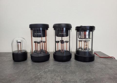歴代の試作機を古い順に左から並べた。アクリルエンクロージャーで密閉させたり、ドライバーを真上に向かせたりすることは、歴代の試作機の多くに共通する特徴だ。中央の有機ガラス製のLED管は当初4本で開発が進められていた。エンクロージャー内部、およびLED管内部にある銅管はそれぞれ通電しており配線の役目を果たしている