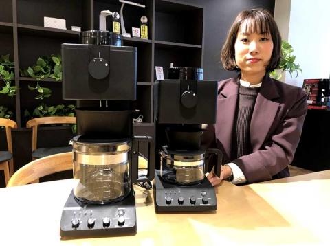 ツインバード工業マーケティング本部マーケティング部の小林氏と、同社の知名度を上げたコーヒーメーカー(左がCM-D465B、右がCM-D457B)