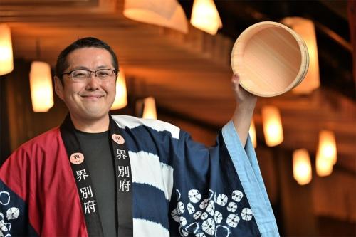 「界 別府」の廣岡太郎総支配人。手にした風呂桶(おけ)は、まさに温泉の街・別府のシンボルだ