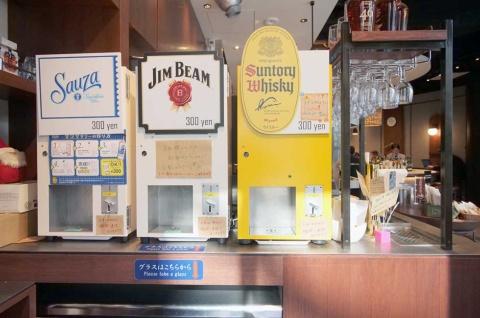 「PRONTO IL BAR 渋谷フクラス店」の立ち飲みスペースに設置された酒類の自動販売機。左からサウザ(テキーラ)、ジムビーム、サントリーウイスキー。手書きの案内を貼って親しみやすい雰囲気を演出している
