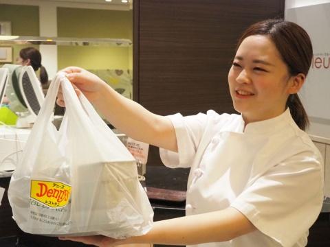 デニーズの宅配専用厨房で調理した料理を配送用の袋に入れて、宅配事業者のスタッフに手渡す