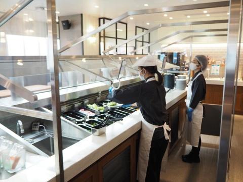 店内の中央にあるサラダバー。客の注文に合わせて従業員が野菜を取り分け、皿をロボットに載せる