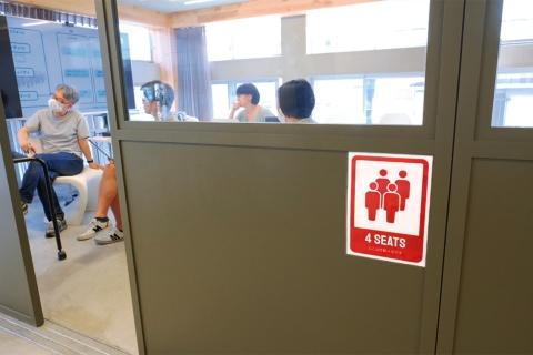 会議室は定員を半分程度に減らし、向かい合わないようにレイアウト。新たなサインを設置し定員を明示している