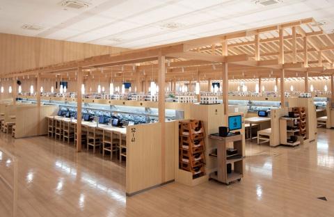 くら寿司「浅草ROX店」の内部。店内に支柱や屋根からなる「やぐら」を組み、その下にカウンターやテーブル、椅子、パーティション、回転寿司の搬送装置をバランスよく配置した。やぐらによる木の味わいがある(写真/丸毛 透)