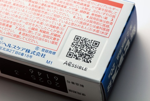 シオノギヘルスケアは医薬品のパッケージに多言語対応のアクセシブルコードを印刷し、「情報」のバリアフリー化を進めている。QRコード部分にはデボス加工を施し、触ると凹(へこ)んでいるのが分かる