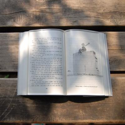 """「BOOK on BOOK」は本のページを開いたままにできるアクリル製の""""透明な本""""。好きなページに乗せるとアクリル越しに本の内容を読むこともできる"""