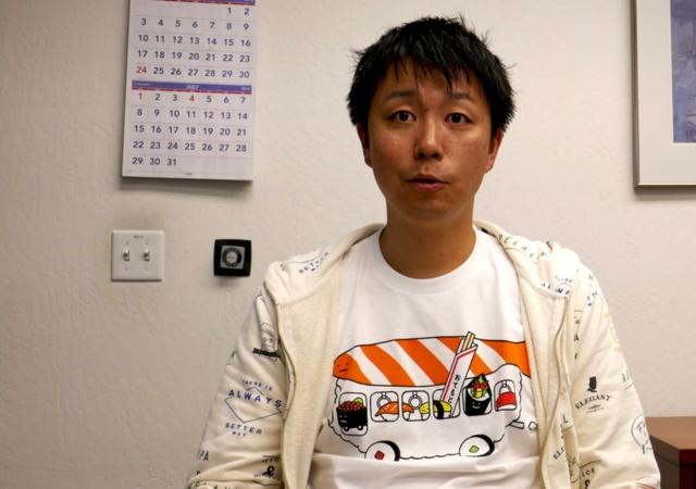 藤巻遼平氏。NECのシリコンバレー拠点にあるデータサイエンス研究所・主席研究員。新会社ドットデータのCEO(最高経営責任者)に就任予定。記者会見などフォーマルな場にも寿司などの日本をイメージするポップなTシャツとパーカー姿で現れる