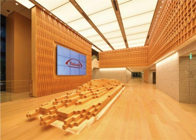 4階のエントランスロビーの中央には、無垢材を集積したベンチがある。壁には、「土」と「木」の文字を配置している