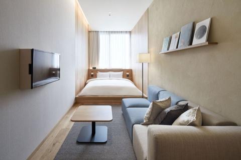 客室数は79室でセミダブルやツインなど9種類を用意。宿泊料金は1万4900~5万5900円(税、サービス料込み)。写真は部屋数が44と最も多い客室(TYPE C)。間口の狭い部屋を広く見せるため、壁掛けテレビを箱で覆うなどの工夫を施している。室内で使われているフロアライト、Bluetooth対応の壁掛けスピーカー、時計、アロマディフューザー、グラス、ドライヤーなどはホテルの下にある店舗「無印良品 銀座」で購入できる