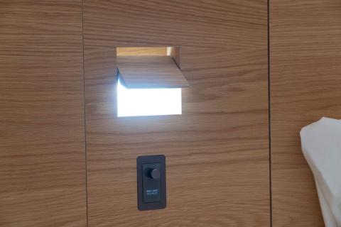 ベッドサイドの照明を壁に埋め込んで目立たないようにしている
