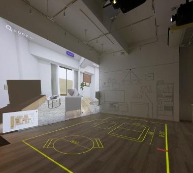 体感型VRモデルルームでは、希望する部屋のイメージをスタイルポートのVR内覧ツール「ROOV walk(ルーブ ウォーク)」による大画面VRで壁に投影できる。それに他社のプロジェクションマッピングを組み合わせた