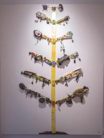 スラム街の中に立てた「E-wasteツリー」というアート作品を模した作品。貼り付けた廃材には家庭用ゲーム機器のコントローラーなどが見える