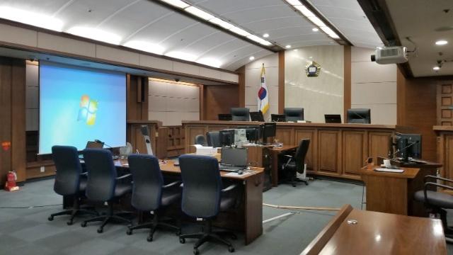 ソウル地方裁判所の電子法廷を視察。日本と異なり米国のように原告・被告が横に並んで着席する。間隔が空いていない。書面は法廷左側の画面に表示される