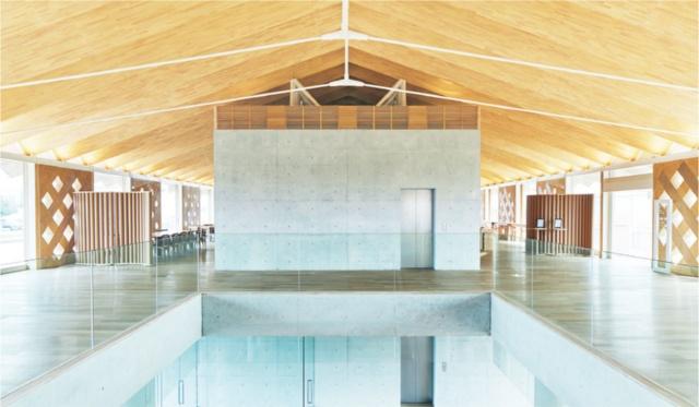共用棟の中央にあるロビー。ジャバラ構造の屋根によって、木造でありながらロングスパンの開放的な空間となっている