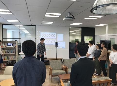 朝会にロボットで参加する楠山氏(中央、スクリーン前に立つ男性の右側)。小型の可動式掲示板のような形だ。プリンシプルは15分程度の朝会を毎朝開催し、クレド(理念を短くまとめたもの)を唱和。グループごとに最近興味を引かれたことや気づいたことを話し、その後、全員の前で数人がプレゼンする
