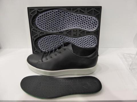 QUANT-U用の靴と3Dプリンターで造形したミッドソール(奥)。ミッドソールは、黒い中敷き(手前)の下に敷いて使用する。ミッドソールの素材は、米ザ・ダウ・ケミカル・カンパニーが開発した液状シリコンゴムを使う