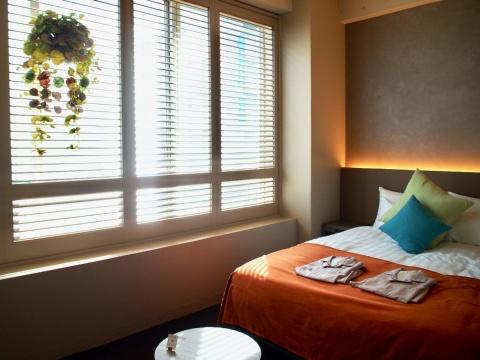 コンパクトなサイズの客室「キタハマアトリエ」。南向きの窓からは木漏れ日が差し、心地良い雰囲気。観光だけでなくビジネスでも利用しやすい