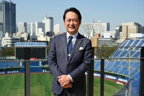 スタジアムのテラス席でみなとみらいの建造物をバックにスタジアムのビジョンを語る岡村社長
