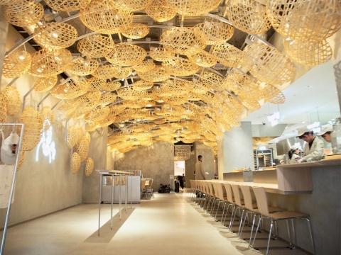 """内装のテーマは""""奥へと導く竹かごの空間""""。六ツ目編みのかごを572個用いて和の繊細さと楽しさを表現したぬくもりのある空間"""