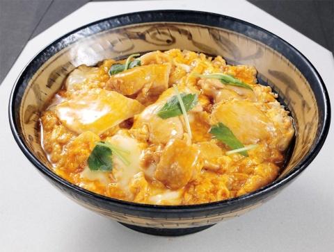 親子丼は漬物とシジミのみそ汁が付いて850円(税込み)。肉を増量して卵黄を乗せた「上」もある(税込み1000円)