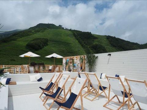ビーチを思わせる施設とリフトのある背景の山との対比が非日常を強調する