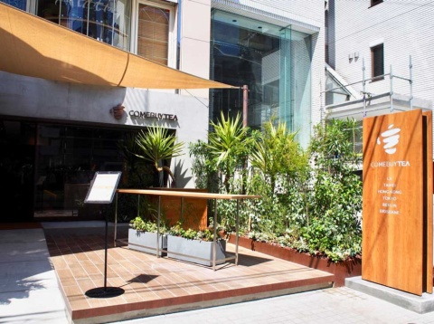 COMEBUYTEA表参道店へは、東京メトロ表参道駅から徒歩3分。原二本通りに面した路面店は、テークアウト需要も意識し、ウッドデッキに緑を配した入りやすい雰囲気
