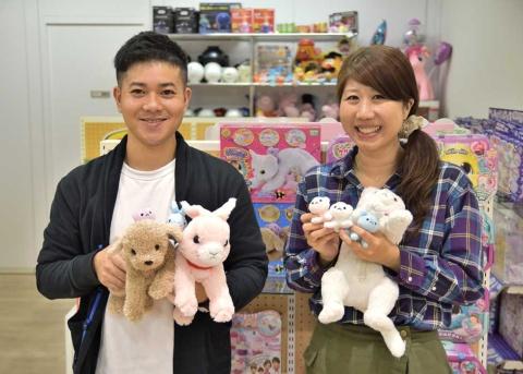 セガトイズ本社のエントランスで商品を抱く土屋氏(左)と伊藤氏。ちなみに「産んじゃったシリーズ」の猫、犬、うさぎのすべての鳴き声と「ハッピーバースデー」の歌は、何人かプロも試したが、結局、開発当時に手伝ってもらった伊藤氏の娘(現在6歳)が本番も担当したという