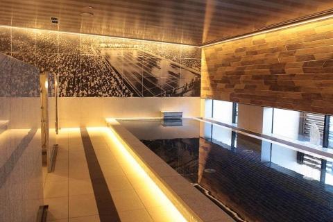 大浴場の壁面アートにはかつての「明治神宮外苑水泳場」の姿が描かれていた。当時の水泳場のタイルを使ったブースもある