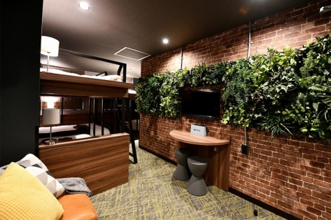 壁を覆うグリーンとレンガ調の壁紙を効果的に使用