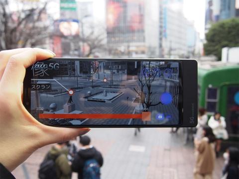 ソニーモバイルコミュニケーションズ製の5G実証実験用スマートフォンを使用。2次元バーコードを読み込んでから渋谷駅前に端末をかざすと、目の前にある街並みに1964年の渋谷の街並みがオーバーラップしたかのように見える