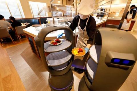 スタッフが皿を搬送ロボットのトレーに置き、席まで届ける。ロボットは本体上部にある赤外線カメラで天井の各所に張り付けられたマーカーを読み取り、ルートを確認しながら移動。今回、店舗には1台約200万円の搬送ロボットを2台導入している